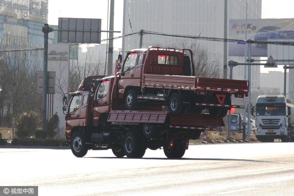 """2017年2月20日,山东滨州,三辆卡车""""叠罗汉""""行驶在国道上。一辆七八米长货车像叠罗汉一样载着两辆同一型号货车,摇摇晃晃开过路口,高度甚至超过了大型客车。"""