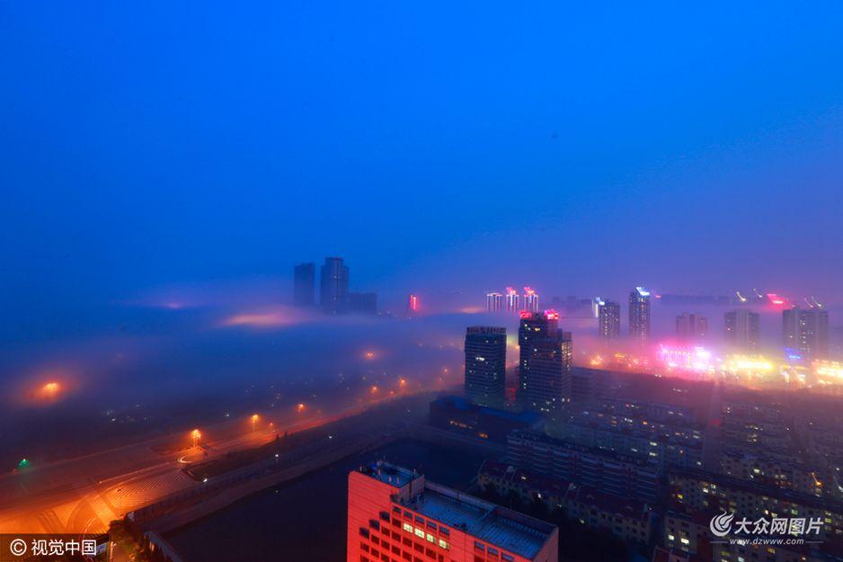 3月11日,日照海边的高层建筑物在平流雾的笼罩下若隐若现,如梦如幻。当日,大雾从大海蔓延至青岛路一线,出现平流雾景观,整个城市在雾海之中若隐若现,在灯光的辉映下,流光溢彩,美轮美奂。