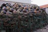 3月30日早晨,青岛西海岸大湾渔港码头上堆满了用来养殖扇贝的网笼和浮球。