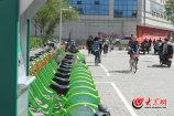 """1、4月18日,在济南泉城路附近,不时有骑着""""小橙车""""的年轻男女经过,""""小绿车""""的舜井街站点处却无人问津。大众网记者 王长坤 摄"""