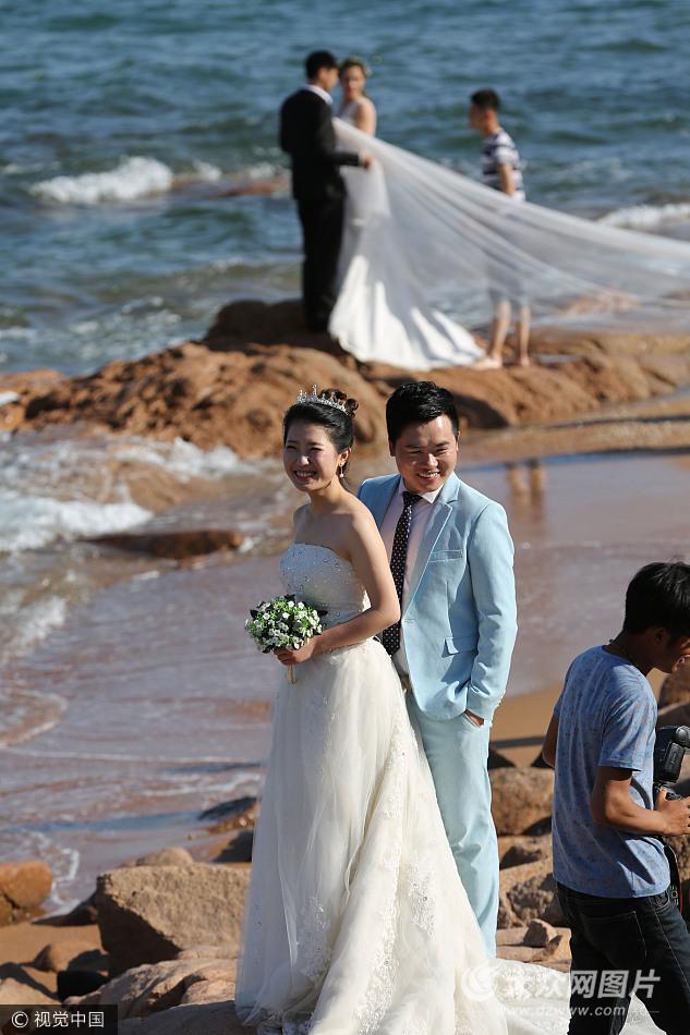 众新人扎堆青岛海水浴场拍摄婚纱照