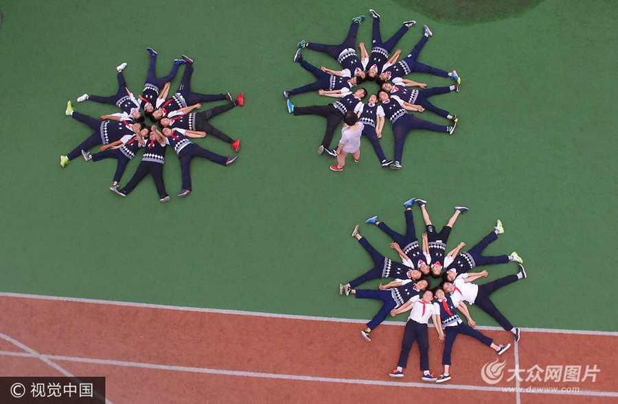 2017年6月9日,在山东济南历下区汇泉小学操场上,百余名小学毕业生躺在操场上摆出各种奇特图形航拍创意毕业照。