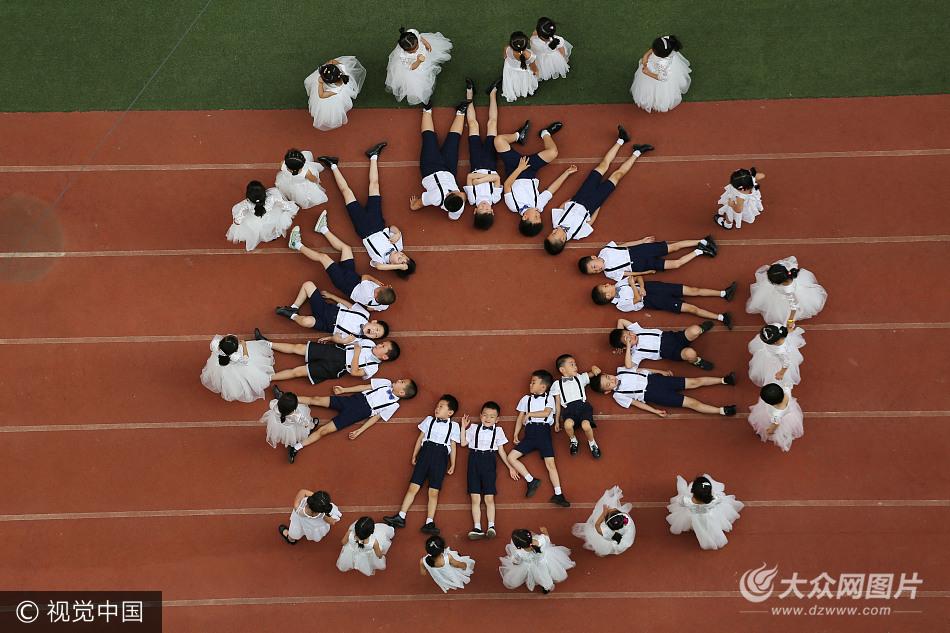 西安一幼儿园组织即将毕业的孩子们在操场上摆出创意新颖的图案拍摄图片