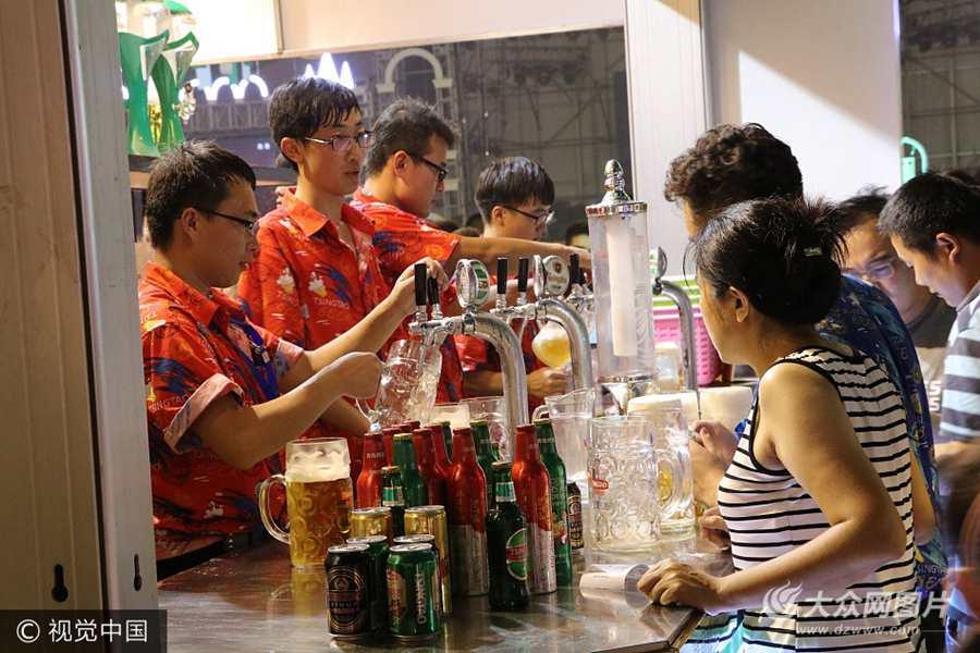 """2017年8月4日晚,黄岛,青岛国际啤酒节主会场在金沙滩盛大开幕。啤酒节开幕式上各个""""啤酒棚""""室内,游客们尽情的畅想各国啤酒。"""