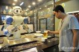 2017年8月6日,山东青岛金沙滩啤酒城,顾客拿起机器人倒入啤酒的啤酒杯。