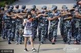 2017年8月31日,山东烟台,一位女士以军训学生为背景拍照留念。