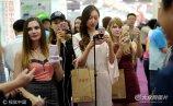 """9月1日,济南,在舜耕会展中心举办的首届""""中华老字号(山东)博览会,,六位中外模特变身网红,手持自拍杆和手机,通过视频直播的方式向各自的""""粉丝""""介绍每一个展位的特色展品。"""