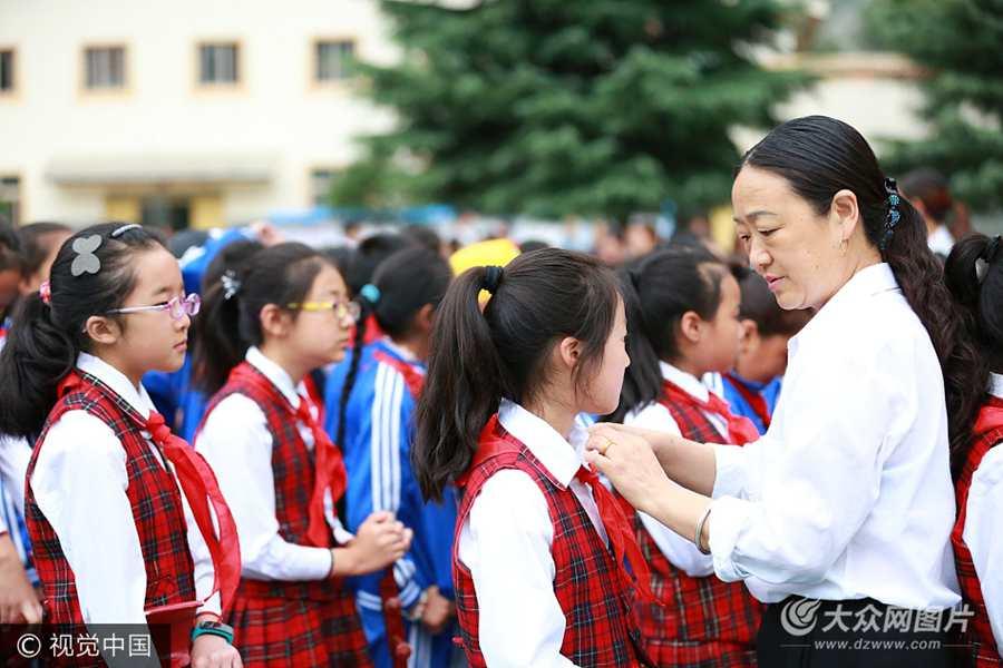 2017年9月1日,四川阿坝州九寨沟第三小学,老师为学生系上红领巾。