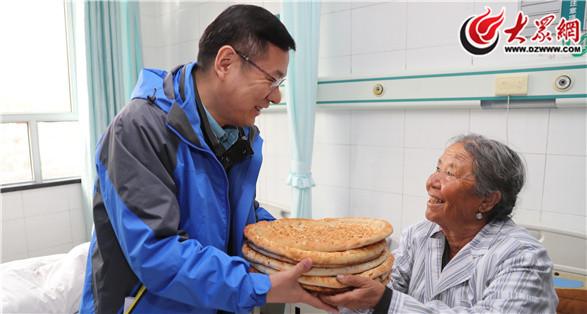 68岁的齐妮罕・巴拉提赠送当地特产馕表示感谢.JPG