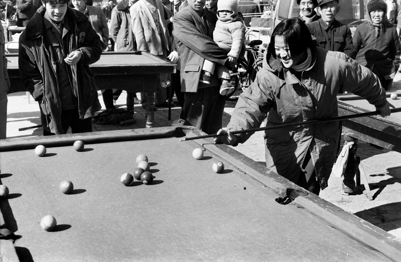 18《城乡台球热》1996年,在滨州惠民的街头,一位20岁左右的女孩在认真地打台球。在上世纪八九十年代,随着市场经济大潮的兴起,城乡居民的娱乐项目日增,台球老少皆宜,桌案一摆就打起来。(田军).jpg