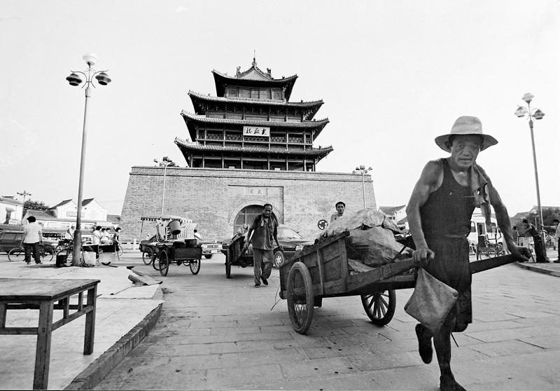 19、《古楼下的板车》1996年8月,聊城市区光岳楼前,两位男子拉着板车依次前行。在他们身后,小轿车慢慢行驶着。在上世纪90年代,进城的商贩运送货物大多采用这样的板车。(林虎).JPG