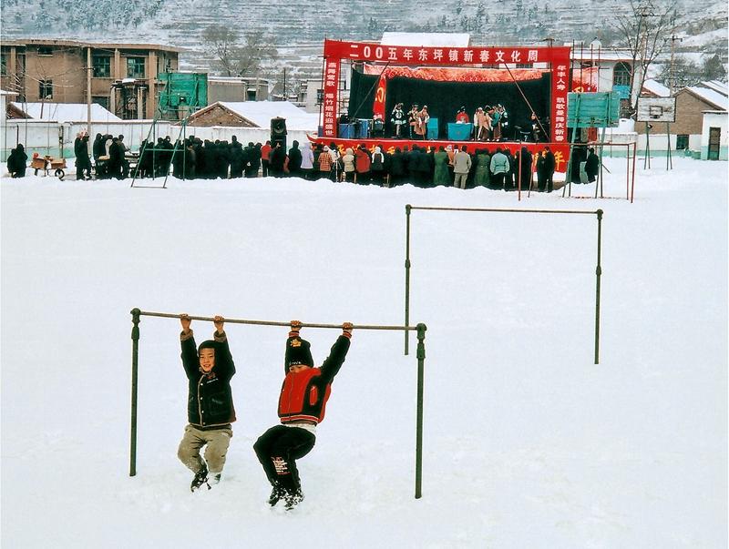 16、《乡镇文化周》2005年,淄博淄川东坪乡,每逢春节假日,淄博市三个剧团都到乡村进行演出活动,这是市五音剧团冒着大雪在东坪进行演出,孩子们看不懂古装戏,就在单杠上玩耍。(刘统爱).jpg