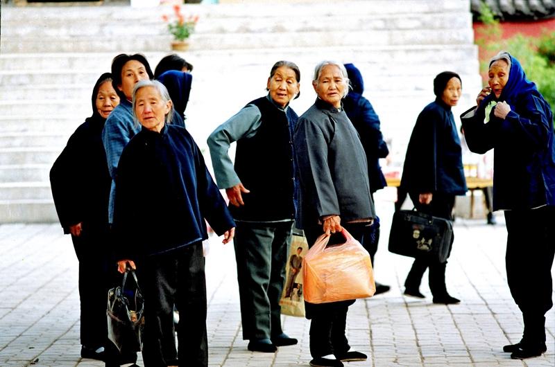 """5、《进城》1992年,山东淄博,一群穿着整洁的老人""""集体出动""""进城逛逛,虽然裹着小脚,但走起路来十分迅捷。城市发展日新月异,让她们感慨不已。(孙伟庆).jpg"""