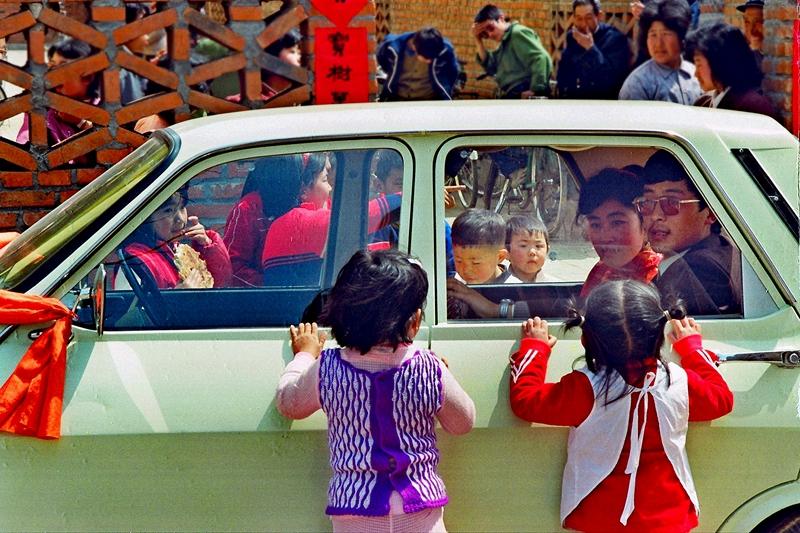 1、《俺想做新娘》1990年,山东烟台,农村青年喜事新办,一辆轿车满载着喜气洋洋的乡情,奔向幸福似锦的未来。这对小姑娘翘首送去祝福的眼光,似乎在说:俺也想做新娘。(兰培喜).JPG