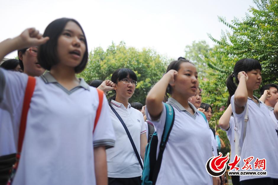 """7月12日,在趵突泉公园内的""""济南惨案纪念堂""""前,济南中学生们面对先烈,举拳宣誓。"""
