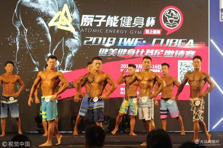 """3月14日,上海世博展览馆,参加女子比基尼组的性感运动美女和男子健体组的肌肉男亮相IWF中国健美健身大赛,不少魔鬼身材的""""眼镜侠""""健美先生获奖引人关注,本次活动也是IWF中国国际健身康体展的重头戏。"""