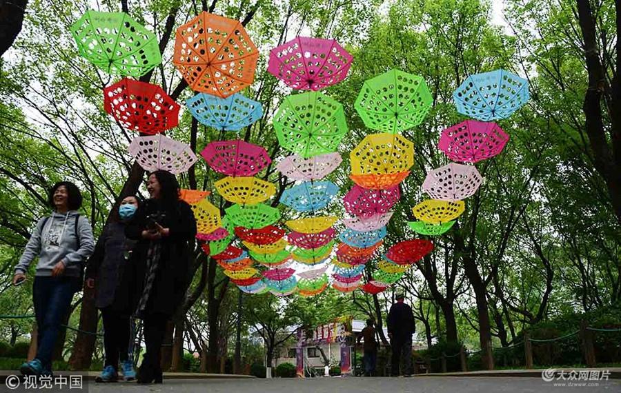 济南:镂空雨伞装饰泉城公园  五彩斑斓