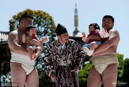"""4月28日,日本东京,心疼宝宝!日本举办宝宝啼哭比赛,相扑选手怀抱萌娃全力比哭。传统的""""婴儿啼哭大赛"""",参赛婴儿在相扑手的怀中比赛啼哭,以向神灵祈求健康。"""