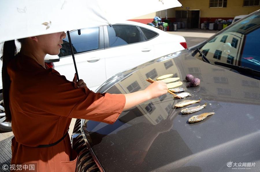 户外烧烤开始啦!气温直逼40度 女子在汽车引擎盖上烤鱼