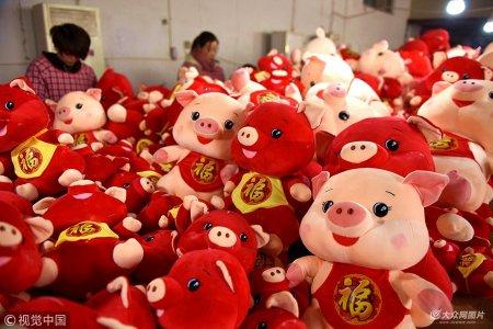 """2018年12月13日,山东临沂,沂南县汉街一家玩具企业工人在忙碌着加工""""富贵猪""""玩具。"""