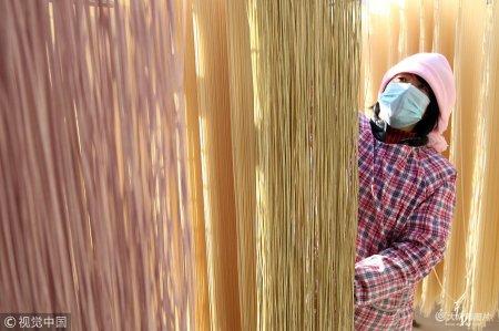 """2018年12月13日,在山东省滨州市博兴县纯化镇周刘村,一名村民正在晾晒制作好的手工""""果蔬挂面""""。"""