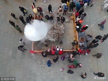 2019年1月12日,山东乳山,市民和游客在围着特制大蒸锅,分享免费海鲜。