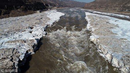 2019年1月21日,山西临汾,受气温回暖影响,冰封的黄河壶口瀑布的冰雪加速融化,部分黄河河道渐渐变宽,初现河水奔腾景象。