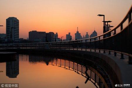 2019年1月22日,寒冬腊月,济南现唯美落日,夕阳的余晖染红了半边天,一排高楼将天际线勾勒出各种线条,泉城广场堪似大片。
