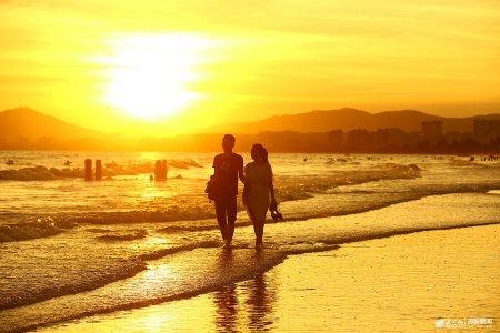 2019年6月6日,海南三亚,一对情侣在三亚湾海边落日余晖中散步。