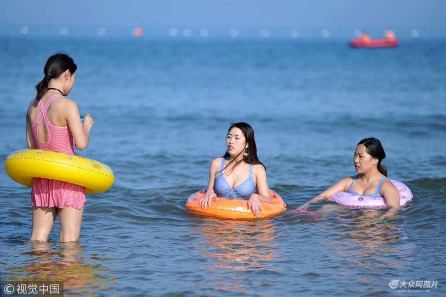 2018年5月31日,众多游客来到山东青岛西海岸新区金沙滩海水浴场,体验初夏时节的海边沙滩风情,还有部分游客等不及海水温度上升率先下到海水中尝鲜游泳带来的快乐。