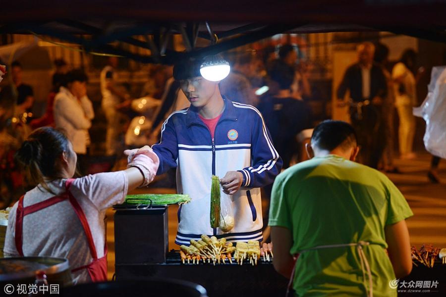 """2018年5月31日,安徽省六安市,夜里11点左右,""""高考工厂""""毛坦厂中学下晚自习的学生陆续走出校门,他们包围着包子铺、麻辣烫、烧烤等路边摊,买些想吃的食物补充体力。"""