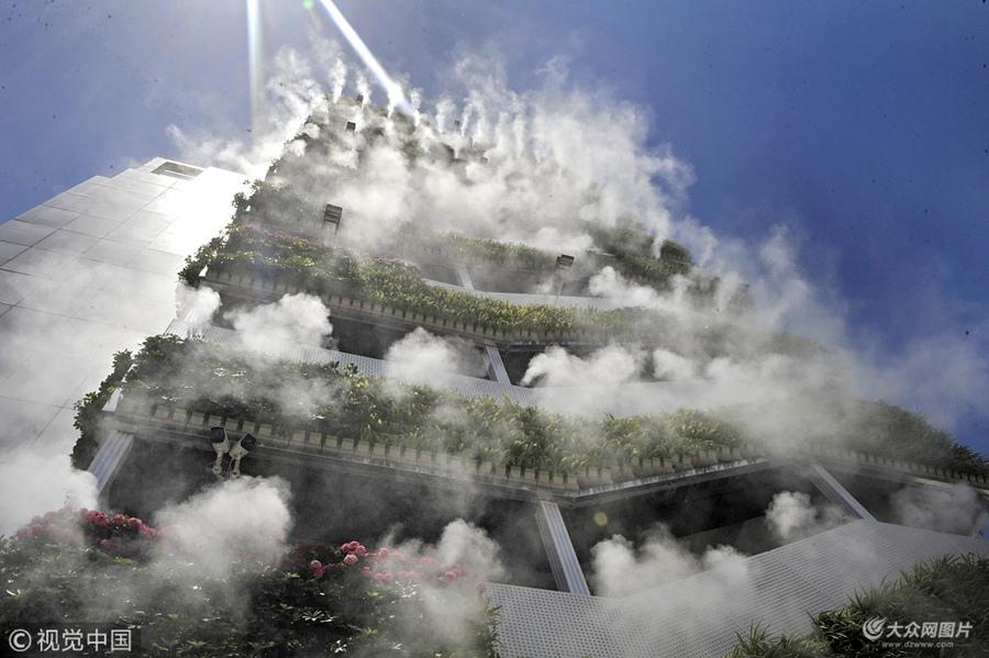 """2018年6月10日,西安,高楼外长满绿植,还萦绕着雾气。一段只有6秒的短视频在抖音火了,网友评论这是""""第四代住房"""",其实这是西安市众创示范街区的一处安装了智能雾森系统的西北最大户外垂直绿化。"""