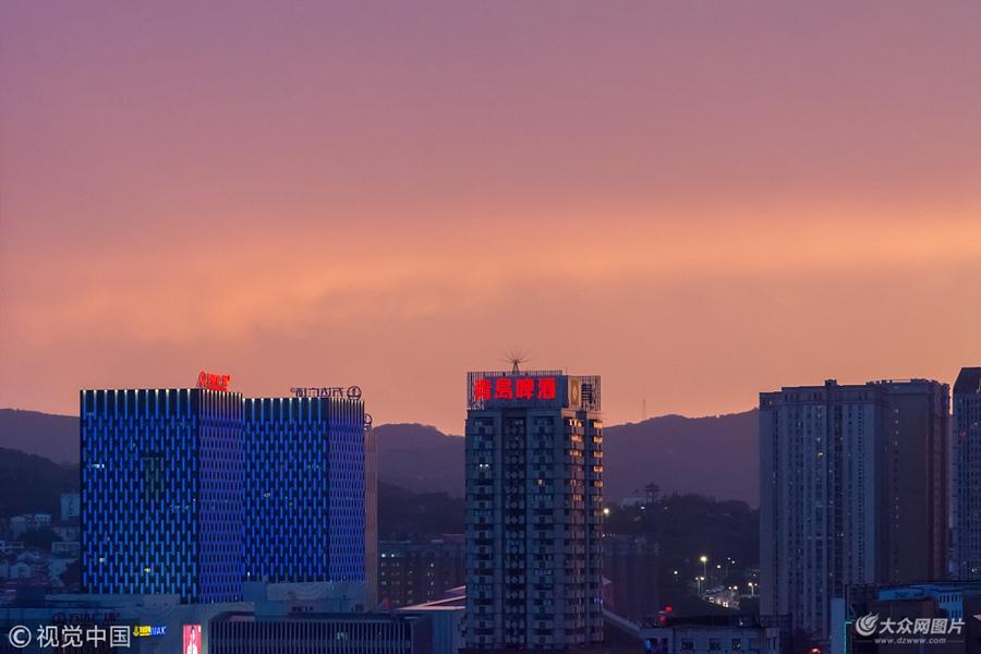 2018年6月13日,山东烟台,雨后西边出现火烧云,落日余晖中霞光万丈,将城市点缀的美如画卷。