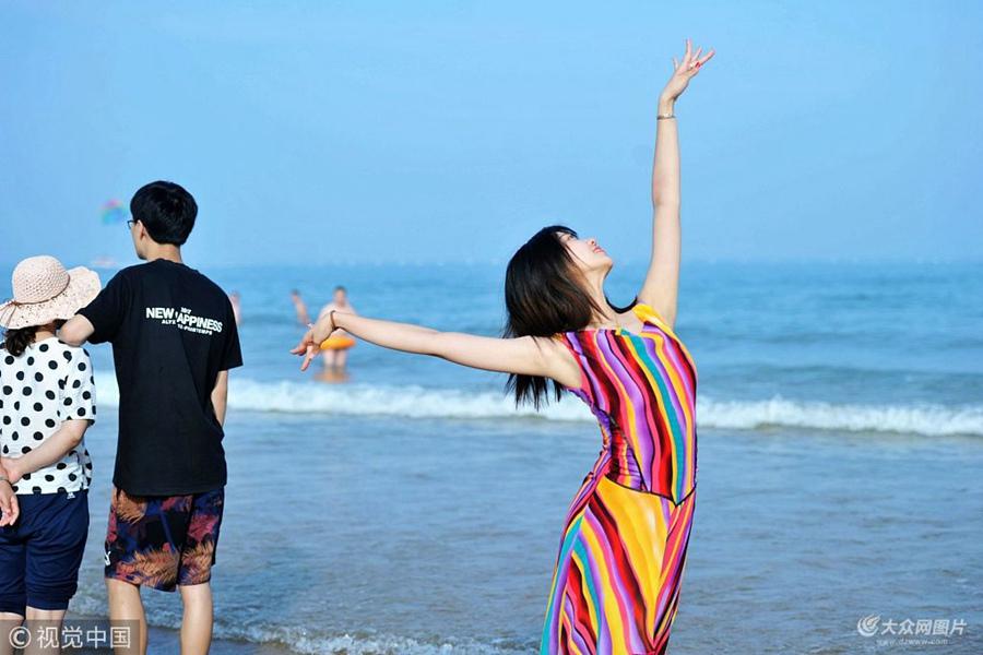 2018年6月24日,青岛西海岸新区金沙滩海水浴场,虽然还没到正式开放时间,但国内外游客已经蜂拥来到这里,享受海水带来的清凉。