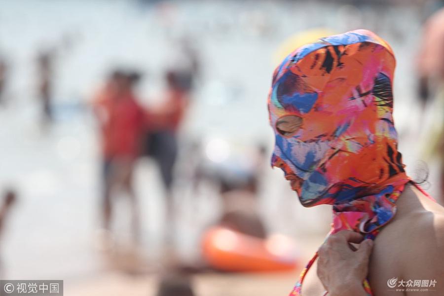 2018年7月6日,脸基尼大妈在青岛第一海水浴场洗海澡。夏日炎炎,防晒神器脸基尼风靡青岛海滩,众多中老年妇女头戴五彩缤纷的脸基尼下海游泳健身,成为一道靓丽的风景。