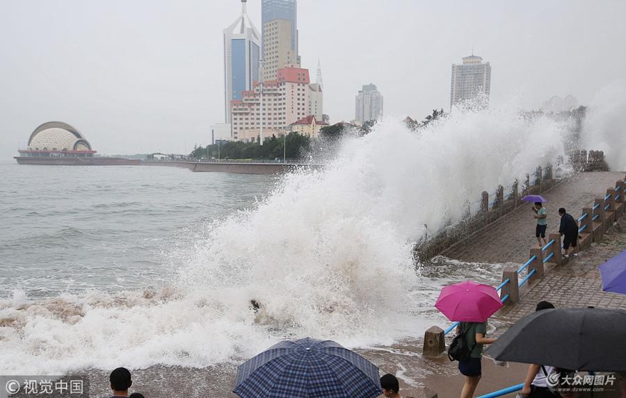 2018年7月10日,游人在青岛栈桥海滨观赏大浪。9日至10日青岛迎暴雨天气,海滨大浪滔天,栈桥景区及多个海水浴场一度关闭,解除危险后开放。