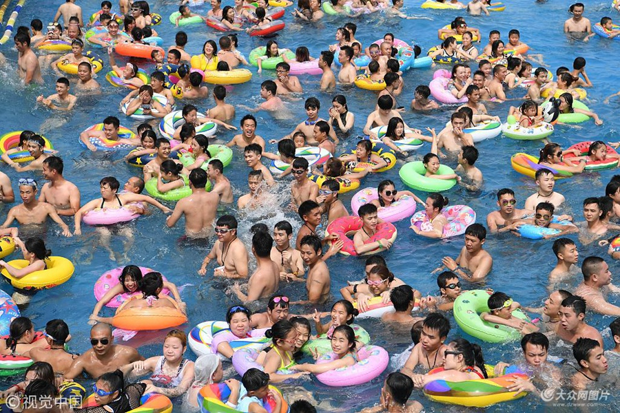 """2018年7月11日,重庆洋人街水上乐园内游客多如""""下饺子"""" 。当日,重庆市气象局发布""""高温橙色预警""""信号。"""