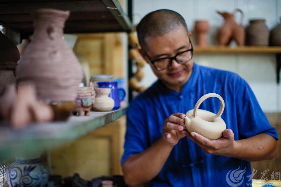 图1 济南市陶瓷艺术大师谷善龙正在欣赏自己的作品圆融壶 大众网记者 毕胜.jpg